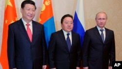From right: Russian President Vladimir Putin, Mongolian President Tsakhiagiin Elbegdorj and Chinese President Xi Jinping pose during their meeting at the sidelines of the Shanghai Cooperation Organization summit in Dushanbe, Tajikistan, Sept. 11, 2014.