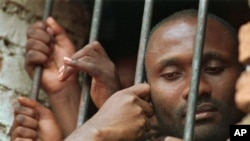 A Hutu man looks out the window of his cell at a Kigali prison Wednesday, April 5, 1995.