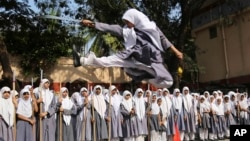 An Indian Muslim girl performs martial arts during a function to mark International Women's Day at a school in Hyderabad, India, Friday, March 7, 2014.