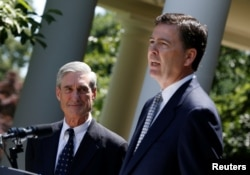 FILE - James Comey, right, speaks alongside outgoing FBI Director Robert Mueller in the Rose Garden of the White House in Washington, June 21, 2013.