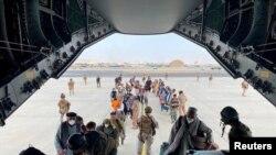 Afganët duke hyrë në avionin transportues
