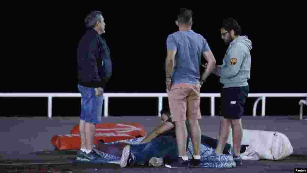 Une personne blessée, assise au sol, est assistée par des passants après l'attaque de Nice, France, 14 juillet 2016.