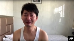 In this image from video taken Feb. 4, 2020 and released by Chen Qiushi, Chinese citizen journalist Chen Qiushi speaks in front of a convention center-turned makeshift hospital amid a viral epidemic in Wuhan in central China's Hubei province. (Courtesy of