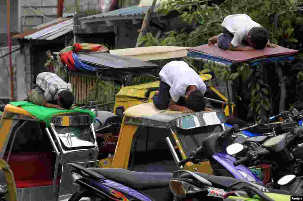 Youths praying atop motorcycle taxis in front of Al-Satie Mosque in Baseco, Tondo city, metro Manila, July 4, 2014.