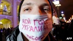 Một người trong đoàn biểu tình phản đối mang chiếc băng với hàng chữ 'Lá phiếu của tôi đã bị đánh cắp tại cuộc đầu phiếu'