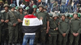 An anti-Mursi protester with an Egyptian flag around his shoulders talks to soldiers standing guard outside the Egyptian presidential palace in Cairo December 9, 2012.