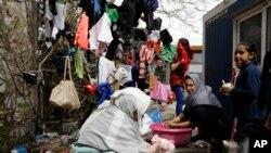 阿富汗妇女在希腊港口城市比雷埃夫斯的难民营里洗衣服。 (2016年3月8日)