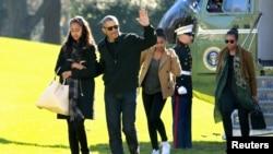 Tổng thống Mỹ Barack Obama vẫy chào khi ông đi cùng Đệ nhất Phu nhân Michelle Obama (phải) và hai người con gái của họ là Malia (trái) và Sasha trên Bãi Cỏ Nam Tòa Bạch Ốc, Washington, ngày 3 tháng 1, 2016.