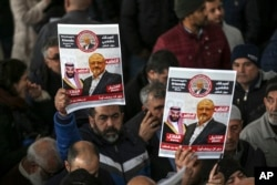 FILE - In this Nov. 16, 2018 file photo, members of Arab-Turkish Media Association and friends of Washington Post columnist Jamal Khashoggi hold posters showing images of Saudi Crown Prince Muhammed bin Salman and of Khashoggi.