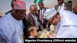 Gwamna Abdullahi Umar Ganduje yayin da ya ke tarben Shugaba Muhammadu Buhari bayan isarsa Kano.
