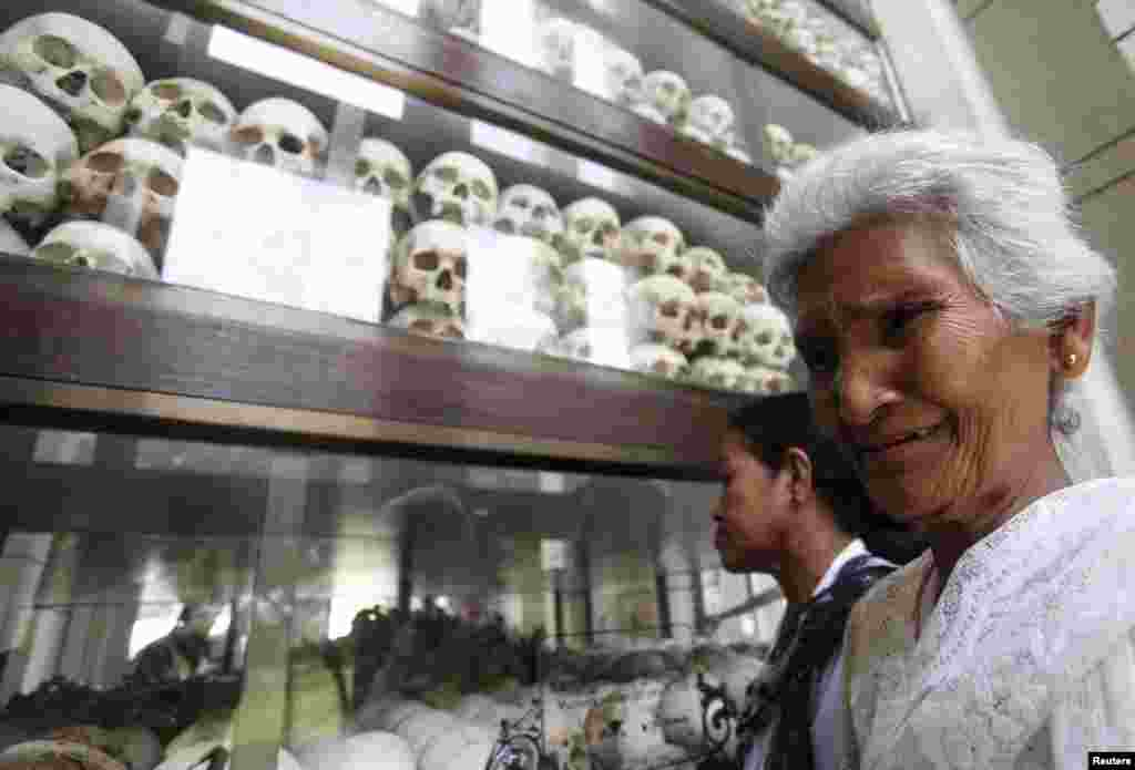 "A woman cries in front of the skulls and bones of more than 8,000 victims of the Khmer Rouge regime during a Buddhist ceremony at Choeung Ek, a ""Killing Fields"" site located on the outskirts of Phnom Penh, Cambodia. Hundreds of Cambodians and monks gathered at the site to commemorate the 40th anniversary of the Khmer Rouge reign."