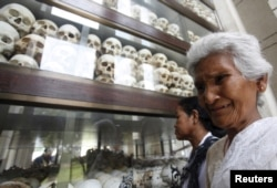 "FILE: A woman cries in front of the skulls and bones of more than 8,000 victims of the Khmer Rouge regime during a Buddhist ceremony at Choeung Ek, a ""Killing Fields"" site located on the outskirts of Phnom Penh, Cambodia, April 17, 2015."