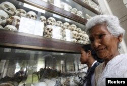 "FILE - A woman cries in front of the skulls and bones of more than 8,000 victims of the Khmer Rouge regime during a Buddhist ceremony at Choeung Ek, a ""Killing Fields"" site located on the outskirts of Phnom Penh, Cambodia, April 17, 2015."