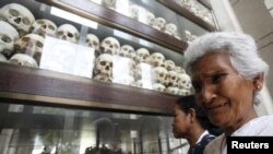 "FILE - A woman cries in front of skulls and bones of more than 8,000 victims of the Khmer Rouge regime at a ""Killing Fields"" site on the outskirts of Phnom Penh, Cambodia, April 17, 2015."