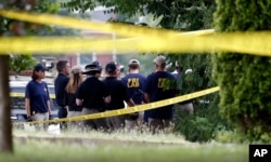 Investigators confer before looking for evidence around the baseball field in Alexandria, Virginia, June 14, 2017, that was the scene of a shooting involving House Majority Whip Steve Scalise, and others.,