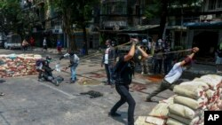 FILE - Anti-coup protesters test a slingshot-type weapon they have made to fight armed Myanmar security forces in Yangon, Myanmar, March 17, 2021.