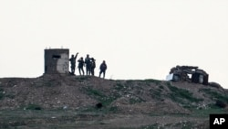 Fighters of People's Protection Units, or YPG, gather at their outpost west of the city of Kobani, northern Syria, Dec. 18, 2018.
