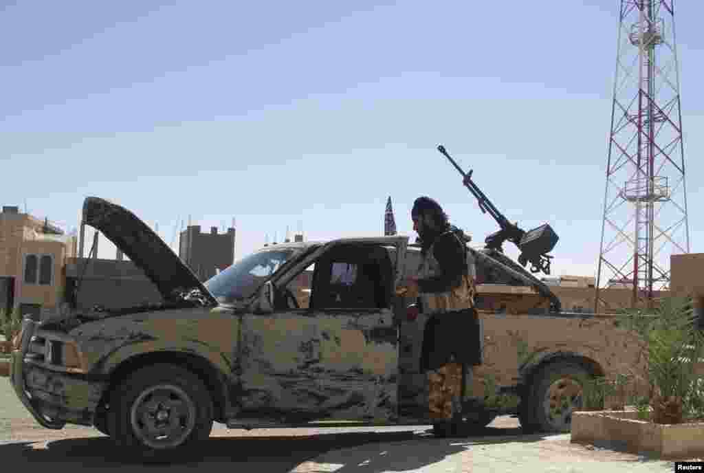 A Free Syrian Army fighter is seen near a vehicle mounted with an anti-aircraft weapon in Al-Sukhna in Homs province, Oct. 20, 2013.