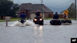 29일 열대성 폭풍 '하비'가 내린 비로 침수된 루이지애나주 레이크찰스 주택가 도로에서 청소년들이 오프로드용 4륜차를 이용해 이동하고 있다.