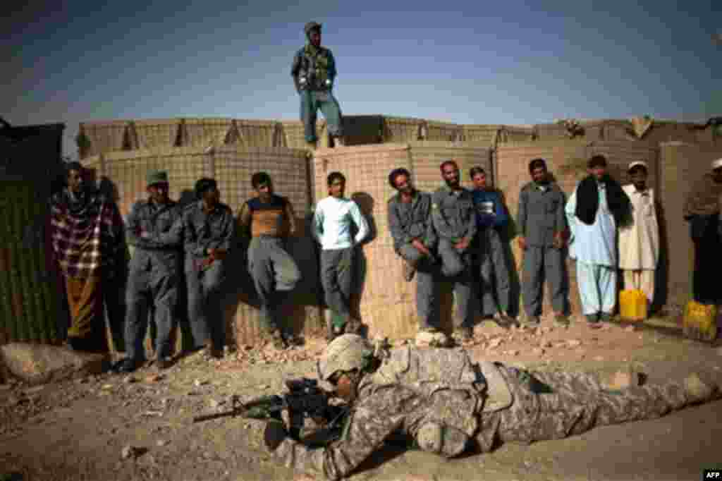 US soldier PFC Mecale Bryant, from Houston, Texas demonstrates firing positions to Afghan policemen on the outskirts of Kandahar City, Afghanistan, Tuesday, Oct. 26, 2010. (AP Photo/Rodrigo Abd)