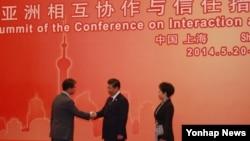 시진핑 중국 국가주석(가운데)이 20일 중국 상하이국제컨벤션센터에서 열린 환영 만찬에 앞서 류길재 통일부 장관(왼쪽)을 맞이하고 있다.