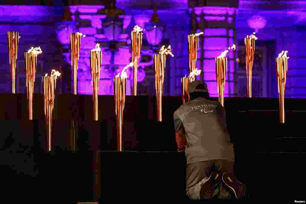 A man places a flame representing one of Japan's prefectures during the Tokyo 2020 Paralympic flame lighting ceremony at the state guest house in Tokyo, Japan.