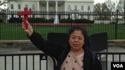 基督徒王春艳举着十字架站在白宫前面(2016年4月2日,对华援助协会网站图片)