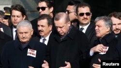Le Premier ministre Binali Yildirim, le président Tayyip Erdogan et l'ancien président Abdullah Gul prient lors d'une cérémonie en hommage aux victimes du double attentat à Istanbul, le 11 décembre 2016.