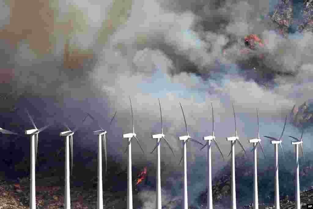 El fuego consume los pastizales y arbustos cerca de los molinos de vientos en Cabazón, California.