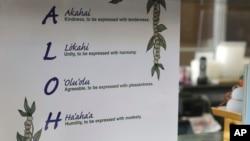 This Tuesday, April 16, 2019 photo shows a sign inside Aloha Poke Shop, in Honolulu, Hawaii that explains 'aloha.' (AP Photo/Audrey McAvoy)