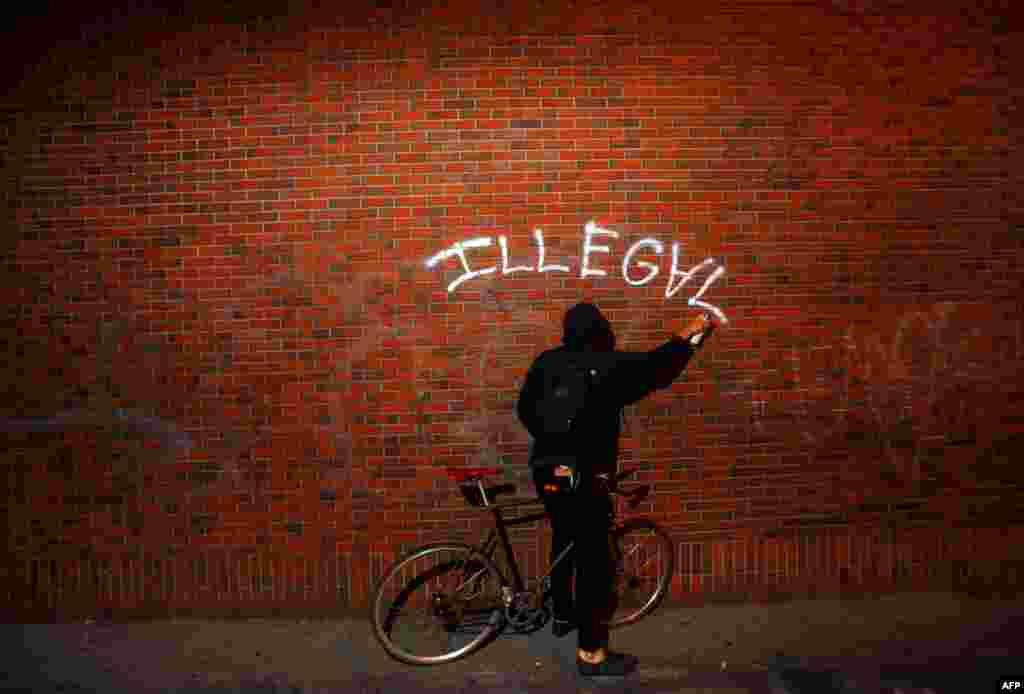 26 tháng 10: Một thành viên trong phong trào Chiếm Lĩnh xịt sơn trong khi có cuộc xuống đường ở thành phố Oakland, California. (AP Photo/Noah Berger)