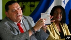 FILE - Francisco Portillo, left, president of the Honduran organization Francisco Morazan, holds up a postcard addressed to President Donald Trump asking to extend Temporary Protected Status for Central Americans and Haitians. He and Marleine Bastien, of Haitian Women of Miami, speak at a news conference in Miami, June 7, 2017.