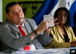Francisco Portillo, left, president of the Honduran organization Francisco Morazan, holds up a postcard addressed to President Donald Trump asking him to extend Temporary Protected Status for tens of thousands of Central Americans and Haitians, as he and Marleine Bastien, right, executive director of Haitian Women of Miami, speak at a news conference in Miami, Florida, June 7, 2017.