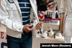 Mantan pembawa bendera dan juara Olimpiade 6 kali, Peter Westbrook, menunjukkan piranti pendingin yang terpasang di seragam resmi Olimpiade timnas rancangan Ralph Lauren, di New York, Rabu, 14 Juli 2021. (Foto: Jeenah Moon/Reuters)