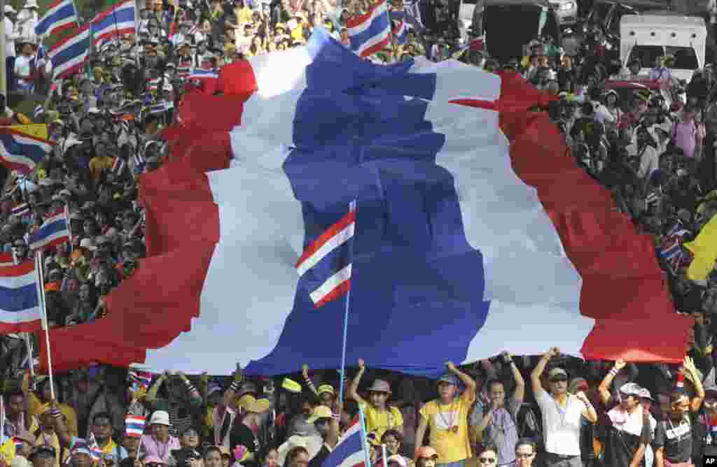 Anti-government protesters carry a huge Thai national flag as they march in Bangkok. Thai Prime Minister Yingluck Shinawatra announced she will dissolve the lower house of Parliament and call elections in an attempt to calm the country's deepening political crisis.