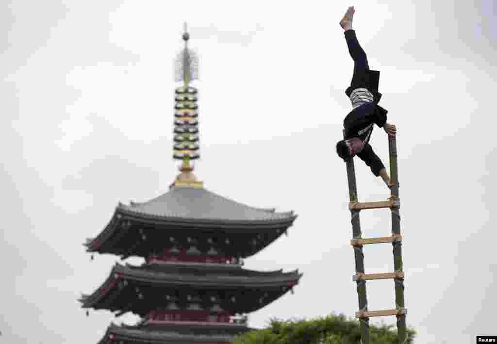 Men wearing traditional firefighter costumes perform acrobatic stunts atop a bamboo ladder following a memorial service for firefighters at Sensoji temple in Tokyo's downtown of Asakusa, Japan.