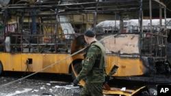 11일 우크라이나 동부 도네츠크 시의 버스 정류장이 폭격을 받은 가운데, 친러시아계 반군이 손상된 버스 옆으로 지나가고 있다.