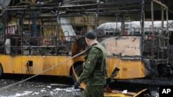 ນັກຕໍ່ສູ້ຫົວແບ່ງແຍກ ທີ່ໄດ້ຮັບການໜຸນຫຼັງຈາກຣັດເຊຍຄົນນຶ່ງ ຍ່າງກາຍລົດບັສຄັນນຶ່ງທີ່ຖືກທຳລາຍ ຈາກລູກປືນໃຫຍ່ ທີ່ຄິວລົດບັສ ທີ່ເມືອງ Donetsk ຢູເຄຣນ ວັນທີ 11 ກຸມພາ 2015.