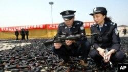 在上海的一次警务活动仪式中警察查看要销毁的仿制枪支。