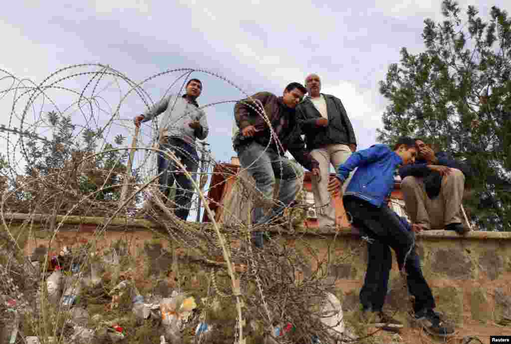 Syrian refugees try to cross the border fence from the northern Syrian town of Ras al-Ain into Turkey during an air strike on Ras al-Ain, in the Turkish border town of Ceylanpinar, Sanliurfa province, Turkey, November 13, 2012.