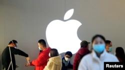 资料照:戴着口罩的人们排队等候测量体温进入一家上海的苹果商店。(2020年2月21日)