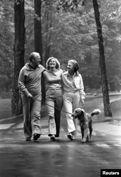 FILE - Former U.S. President Gerald R. Ford (left), daughter Susan (center) and his wife first lady Betty Ford (right) and their dog Liberty walk at the presidential retreat Camp David in Maryland, Aug. 7, 1976.