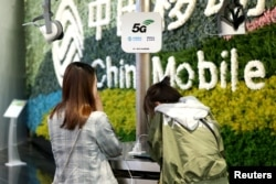 FILE - Customers are seen at a China Mobile flagship store displaying smart home experience with 5G network, in Shanghai, China, March 10, 2019.