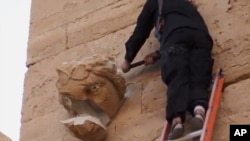 A militant hammers at a sculpted face in the ancient Iraqi city of Hatra in this scene from an Islamic State militant video posted on YouTube, April 3, 2015. The fortified city is recognized as a UNESCO World Heritage site.