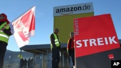 Employees of U.S. online retailer Amazon rally during a strike in front of one of the company's logistics centers, in Graben, Germany, Dec. 16, 2013.