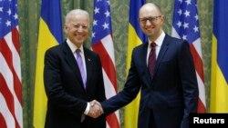 El vicepresidente Joe Biden estrecha la mano al primer ministro ucraniano, Arseniy Yatsenyuk, durante su visita a Kiev.