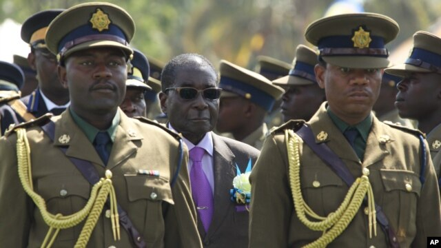Zimbabwean President Robert Mugabe (C) inspects the honor guard during a police parade in Harare, June 13, 2013.