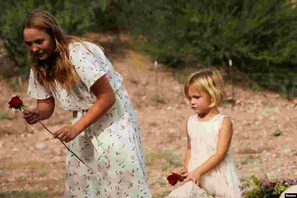 Una niña sostiene una flor durante el funeral de Dawna Ray Langford y sus hijos Trevor, Rogan.