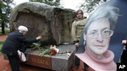 A 2009 file photo shows a man holding a portrait of killed journalist Anna Politkovskaya as a woman lays flowers during a commemorative rally in St.Petersburg