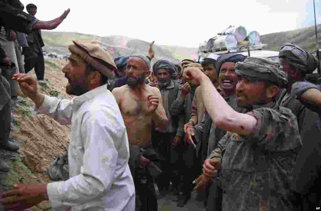 Afghanis show their injuries to local and international journalists after police fired shots into the air to disperse a crowd that had rushed toward a truck carrying aid, near the site of the landslide that buried Abi Barik village in Badakhshan province, northeastern Afghanistan, May 6, 2014.